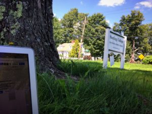Photo of computer sitting on grass underneath a maple tree, with Sterling sign in background